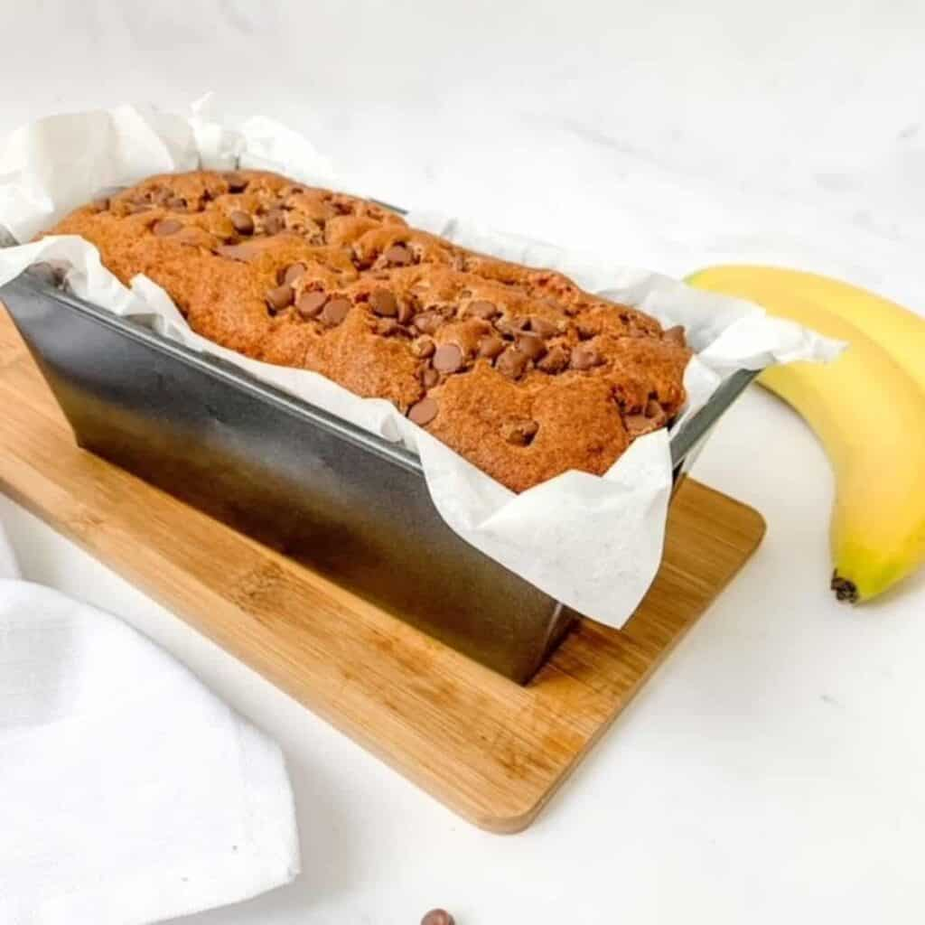 finished banana bread in baking tin beside two bananas