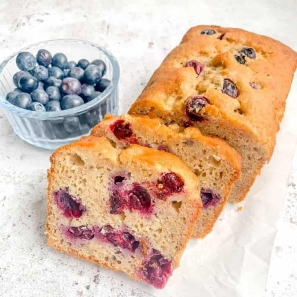 Gluten free blueberry banana bread with two pieces sliced with a small bowl of blueberries