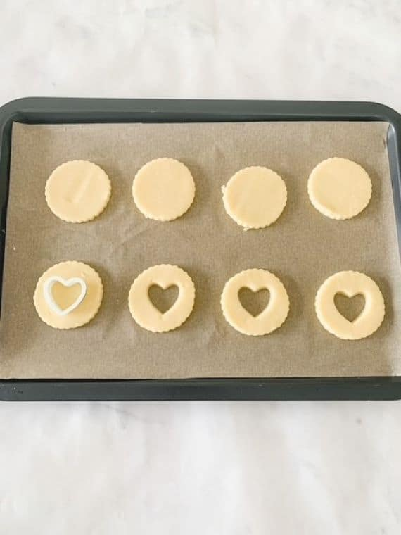 round shortbread dough on a baking tray with a heat shape cookie cutter