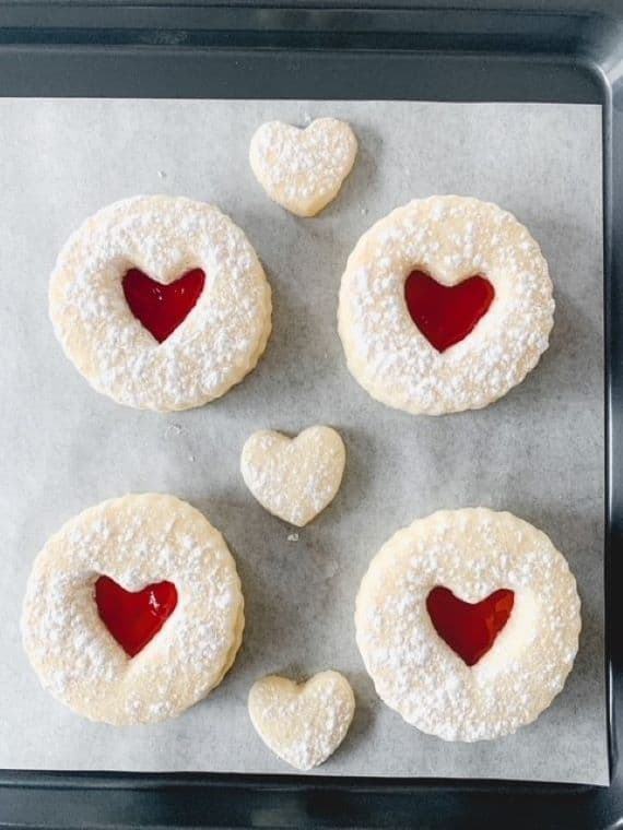 gluten free jammie dodgers on a baking tray sprinkled with icing sugar